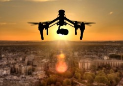 Drone silhouette flying above Paris city panorama in sunset