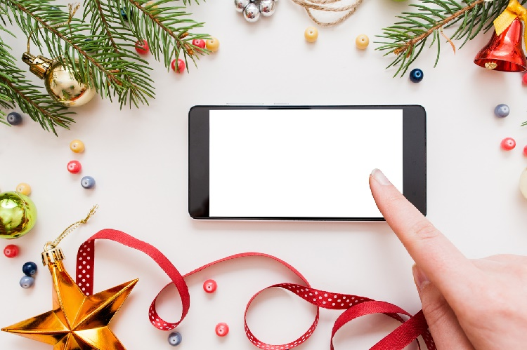 Woman using smartphone with blank screen, festive trumpery frame. Christmas gift search, online shopping, seasonal discounts and sale concept