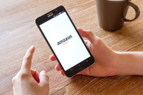 Chiang Mai, Thailand - April 26, 2016: man hand holding screen shot of Amazon application showing on Asus Zenfone 2 mobile phone. Amazon is an American international electronic commerce company.