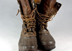 Vintage leather and rubber winter snow or rain boots. Studio shot on a gray background.